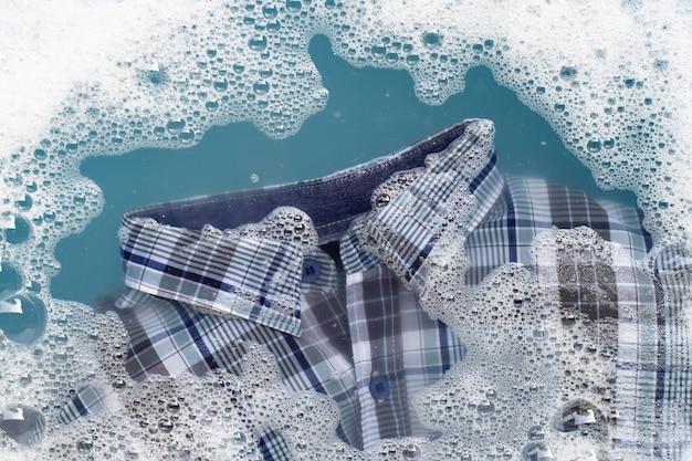 Das hemd in wasser mit waschmittelpulver einweichen Premium Fotos