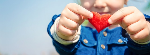 Das herz liegt in den händen des kindes. tiefenschärfe. Premium Fotos