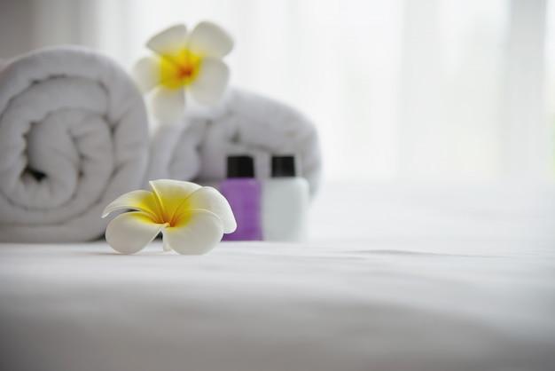 Das hoteltuch und die shampoo- und seifenbadflasche, die auf weißes bett mit der plumeriablume verziert wurden - entspannen sie sich ferien am hotelerholungsortkonzept Kostenlose Fotos