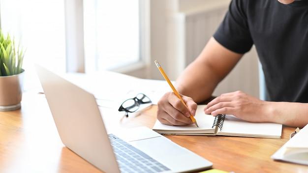 Das hs des nahaufnahmemannes, das auf notizbuchpapierlaptop schreibt. Premium Fotos