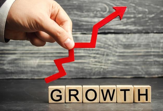 Das inschriftenwachstum und der aufwärtspfeil. das konzept eines erfolgreichen unternehmens. einkommenssteigerung Premium Fotos