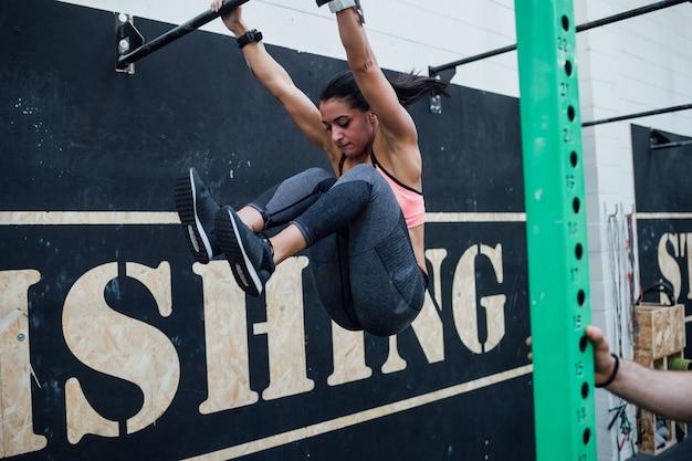 Das junge atletic frauenhandeln zieht an der gymnastischen stange hoch, die vom persönlichen trainer geholfen wird Premium Fotos