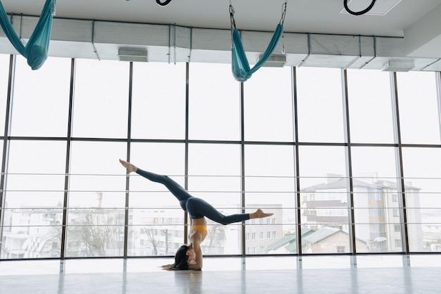 Das junge attraktive mädchen, das eignung tut, trainiert mit yoga auf dem boden. panoramafenster Premium Fotos