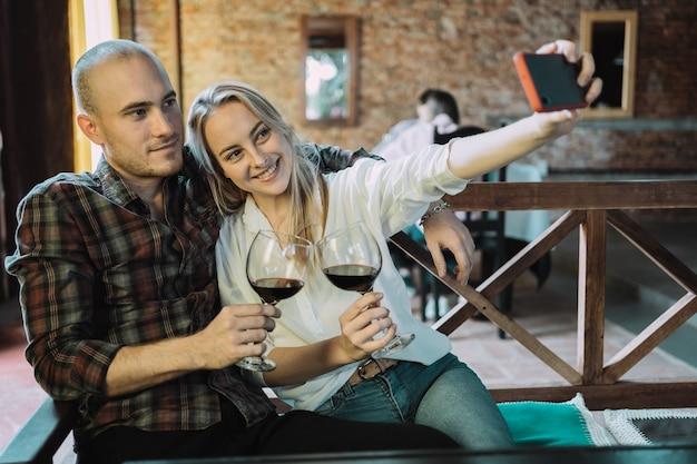 Das junge paar stößt mit einem glas wein an, während es ein selfie herausnimmt. Premium Fotos