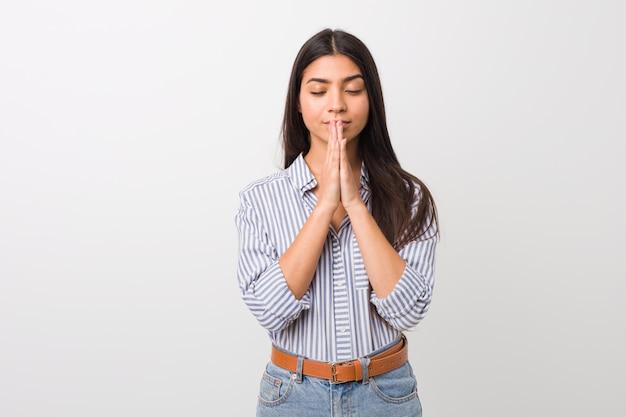Das junge recht arabische frauenhändchenhalten beten herein nahe mund, glaubt überzeugt. Premium Fotos