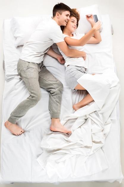 Das junge schöne paar liegt in einem bett Kostenlose Fotos