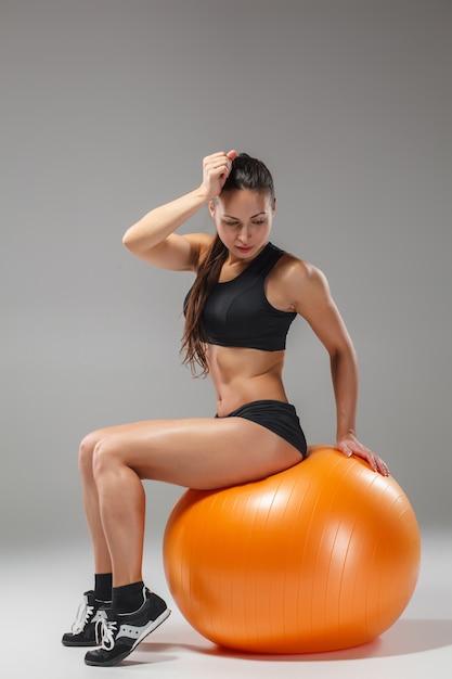 Das junge, schöne sportmädchen macht übungen auf einem fitball Kostenlose Fotos