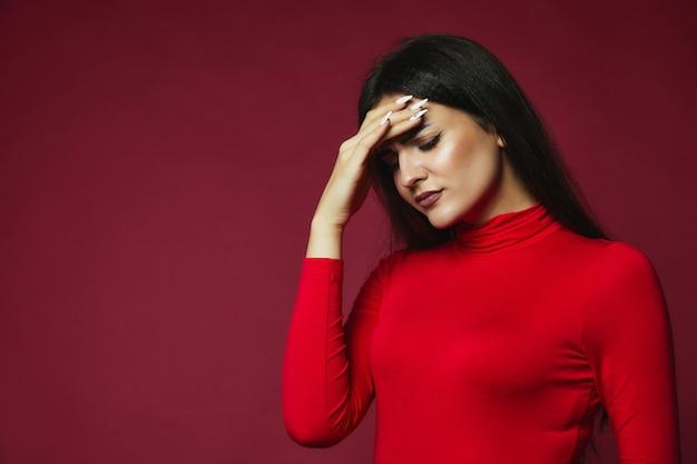 Das kaukasische mädchen des umgekippten brunette, das im roten pullover mit ärgerlichen kopfschmerzen gekleidet wurde, setzte hand auf die stirn Kostenlose Fotos