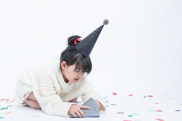 Das kind, das einen schwarzen partyhut trägt, hat spaß. weißer hintergrund und schwarzer hut passen gut zusammen. Premium Fotos