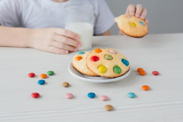 Das kind isst gerne hausgemachte kekse mit milch Premium Fotos