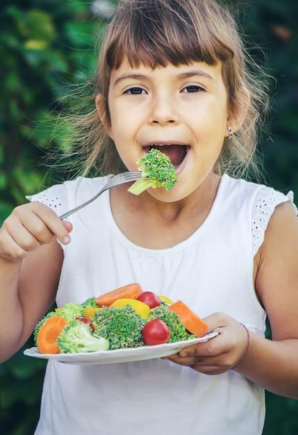 Das kind isst im sommer gemüse. selektiver fokus. menschen. Premium Fotos