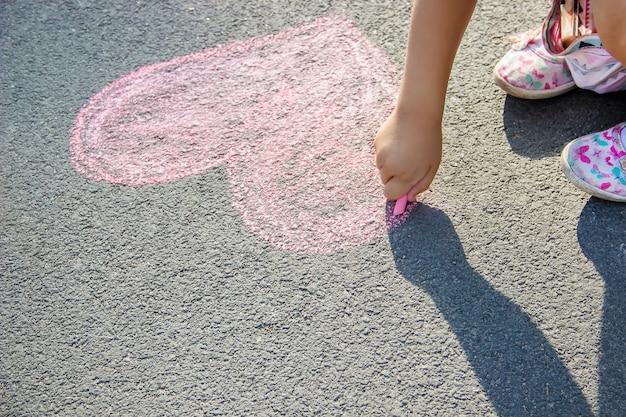 Das kind malt kreide auf das asphaltherz. selektiver fokus Premium Fotos