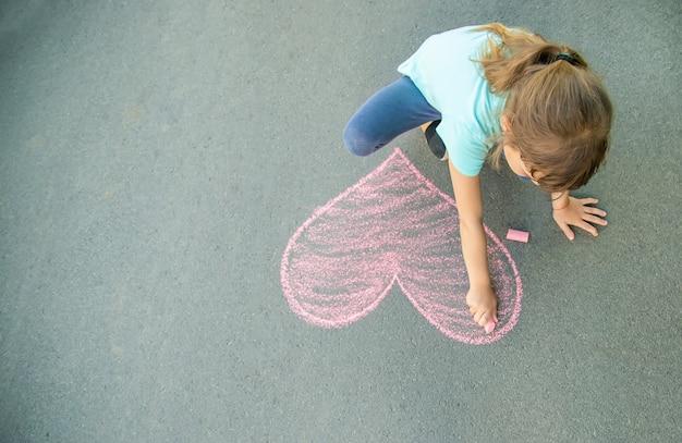 Das kind malt kreide auf das asphaltherz. tiefenschärfe. Premium Fotos