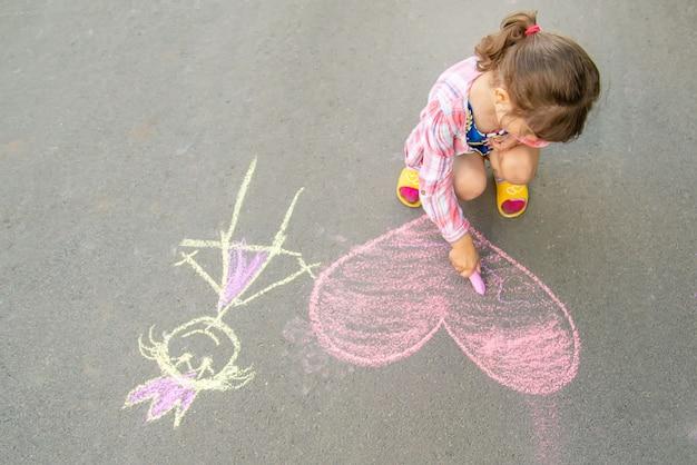 Das kind malt kreide auf das asphaltherz. Premium Fotos