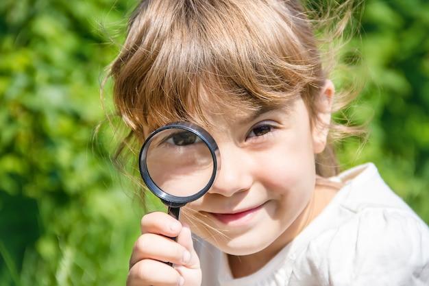 Das kind schaut in eine lupe. erhöhen, ansteigen. Premium Fotos