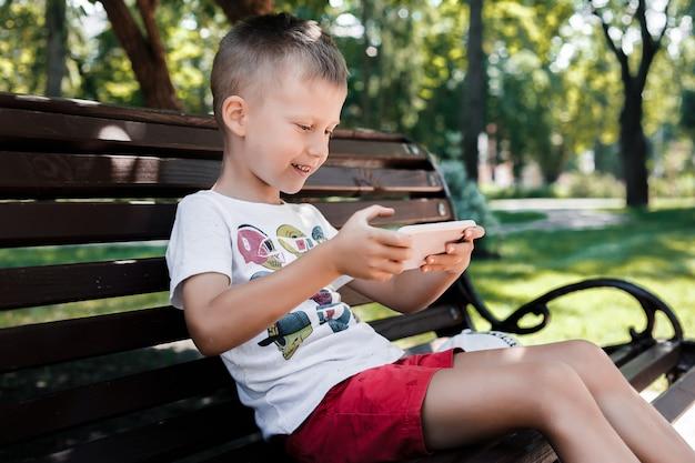 Das kind sitzt im park auf einer bank mit einem gerät. kinder benutzen geräte. ein junge spielt ein spiel auf einem handy. Premium Fotos
