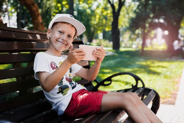 Das kind sitzt im park auf einer bank mit einem gerät. kinder benutzen geräte. porträt eines schönen jungen in der untergehenden sonne. ein junge spielt ein spiel auf einem handy. Premium Fotos