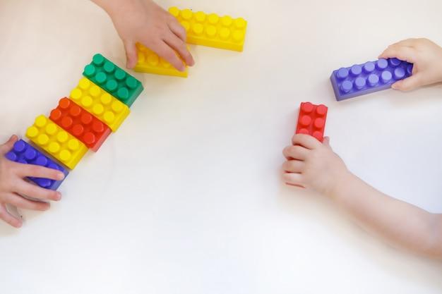 Das kind spielt mit bunten details des konstrukteurs. spielzeug in der hand. konzept der entwicklung von feinmotorik, lernspielen, kindheit, ivf, kindertag, kindergarten. speicherplatz kopieren Premium Fotos