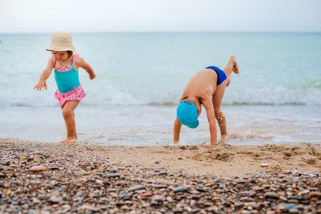 Das kind spielt und spritzt im meer Premium Fotos