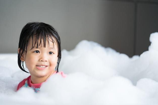 Das kleine asiatische Mädchen, das im Jacuzzi am Badezimmer mit ...
