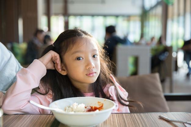 Das kleine asiatische mädchengefühl langte das lebensmittel mit der reis- und tomatensauce Premium Fotos