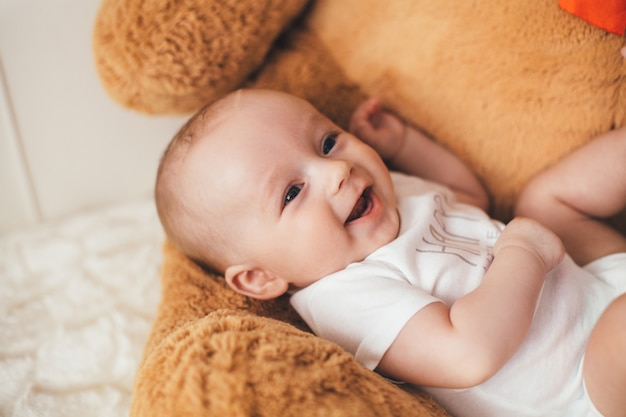 Das kleine baby liegt auf dem bären Kostenlose Fotos