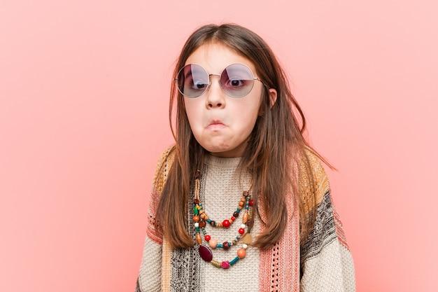 Das kleine hippie-mädchen zuckt verwirrt mit den schultern und den offenen augen. Premium Fotos