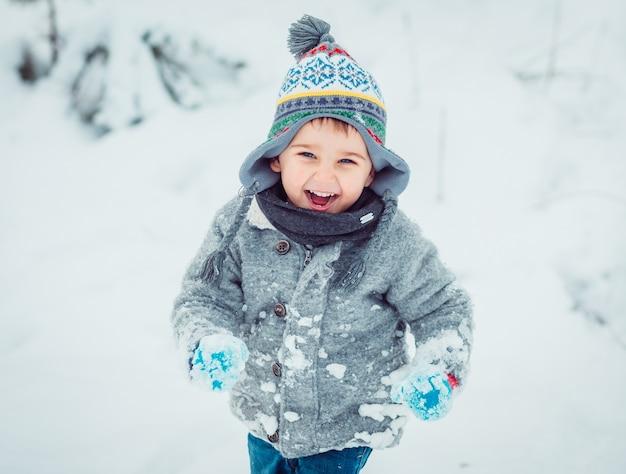 Das kleine kind, das entlang schnee läuft Kostenlose Fotos