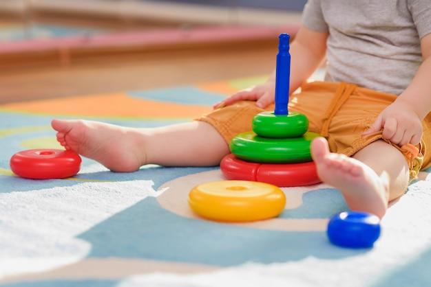 Das kleine kind sammelt eine pirimda, die auf einem fußboden sitzt Premium Fotos