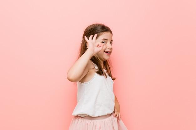 Das kleine mädchen, das einen prinzessinblick trägt, blinzelt ein auge und hält eine okaygeste mit der hand. Premium Fotos