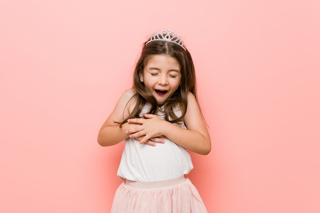 Das kleine mädchen, das einen prinzessinblick trägt, lacht glücklich und hat spaß, hände auf magen zu halten. Premium Fotos