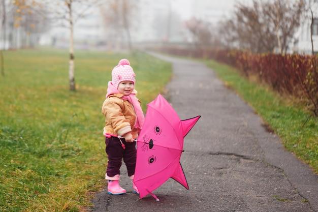 Das kleine mädchen mit einem regenschirm im herbst Premium Fotos