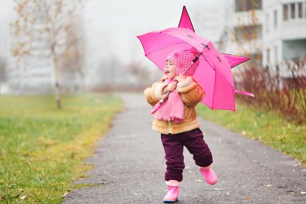 Das kleine mädchen unter einem regenschirm im herbst Premium Fotos