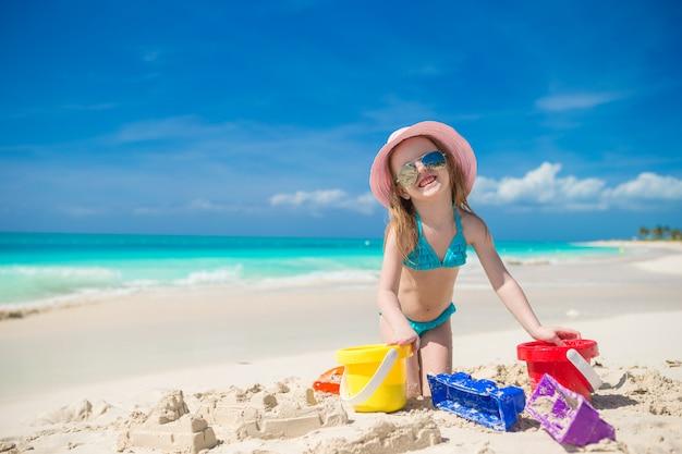 Das kleinkind, das mit strand spielt, spielt während der tropischen ferien Premium Fotos