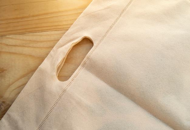 Das konzept der aufgabe von plastiktüten, eco-bag aus vliesstoff, lag flach auf hellem holzuntergrund Premium Fotos