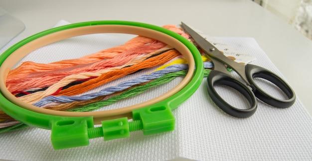 Das konzept der handarbeit. nähzubehör für stickleinwand, stickrahmen, garn Premium Fotos