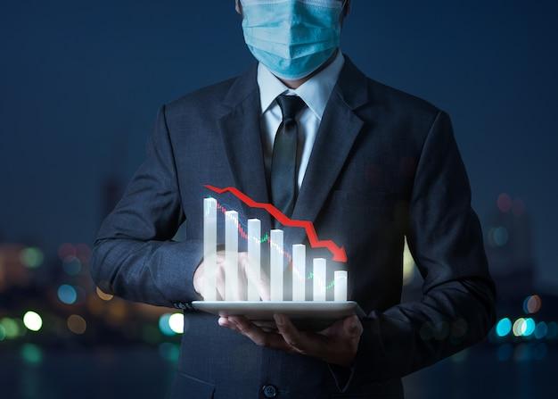 Das konzept der pfeile der wirtschaftskrise fällt, der aktiensturz des grafikers zeigt auf dem tablet mit dem geschäftsmann, was auf die wirtschaftliche rezession hinweist, die eintreten wird Premium Fotos