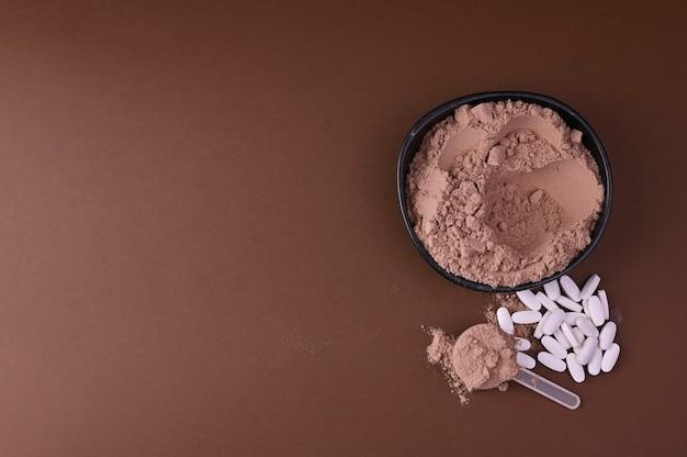 Das konzept der sporternährung und bio-nahrungsergänzungsmittel. pillen und protein im pulver auf einem schwarzen hintergrund. speicherplatz kopieren. Premium Fotos