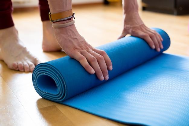 Das konzept der yoga-und fitness-matte in den händen. Premium Fotos