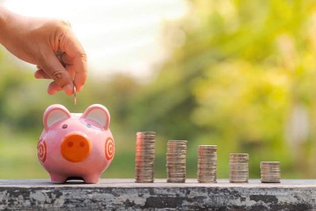 Das konzept des einsparens des geldes, hand, die eine münze in sparschwein über unscharfem gartenhintergrund setzt Premium Fotos