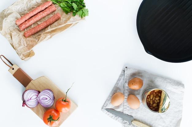 Das konzept des kochens eines englischen frühstücks auf einem weißen hintergrund und einem raum für text. Premium Fotos