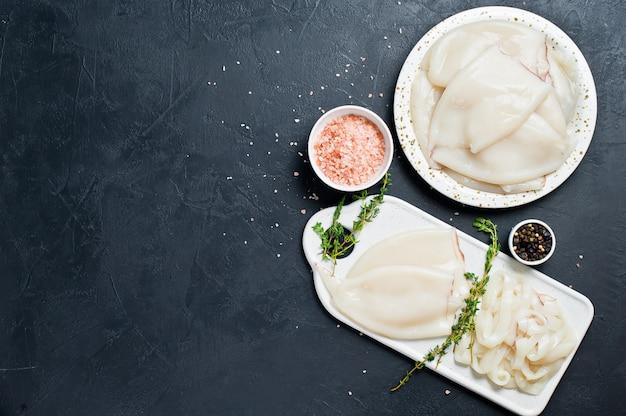 Das konzept des kochens rohen tintenfisch zutaten zum kochen thymian, pfeffer, rosa salz Premium Fotos