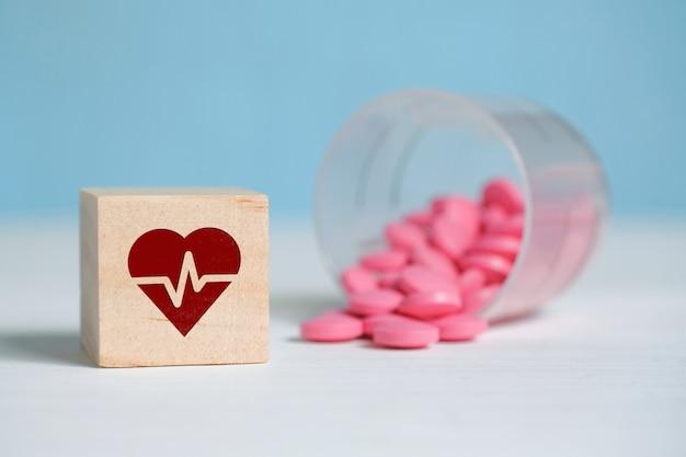 Das konzept einer täglichen medikamentendosis für das herz. ikone auf einem holzquadrat neben tabletten aus plastikbecher. Premium Fotos