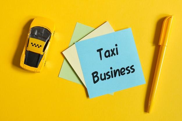 Das konzept eines taxis als geschäft. spielzeugauto auf einer gelben wand mit einem aufkleber. draufsicht. Premium Fotos