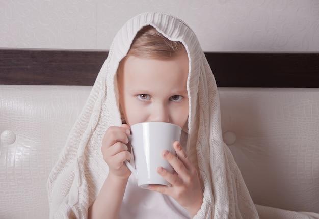 Das kranke kind sitzt in einem bett und hält eine tasse tee Premium Fotos