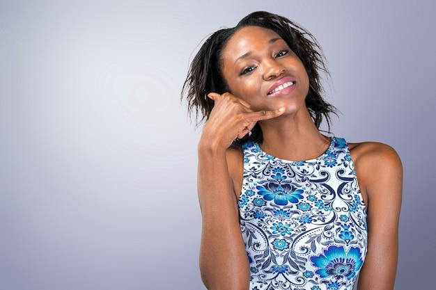 Das lächelnde afrikanische frauenhandeln ruft mich zeichen an Premium Fotos