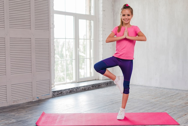 Das lächelnde mädchen, das im yoga steht, werfen auf einem bein auf Kostenlose Fotos