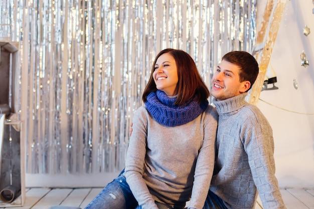 Das lächelnde paar in winterkleidung schaut auf die linke seite des fotos Premium Fotos