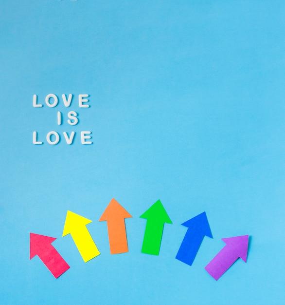 Das layout von papierpfeilen in lgbt-farben und liebe ist liebeswörter Kostenlose Fotos