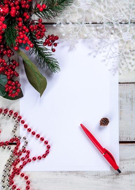 Das leere blatt papier auf dem holztisch mit einem stift und weihnachtsschmuck. Kostenlose Fotos